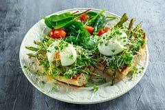 健康早餐捣毁了鲕梨、芦笋和荷包蛋在烤多士早餐供应用沙拉和李子 免版税库存图片