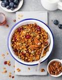 健康早餐新鲜的格兰诺拉麦片,与南瓜籽,在白色碗的山核桃果的muesli 顶视图 免版税库存图片