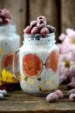 健康早餐是与chia种子、龙舌兰糖浆、牛奶、无花果和莓和蓝莓冷冻莓果的布丁  库存图片