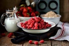 健康早餐是新鲜的有机莓、草莓与燕麦剥落和牛奶在老木背景 土气样式 免版税库存图片