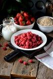 健康早餐是新鲜的有机莓、草莓与燕麦剥落和牛奶在老木背景 土气样式 图库摄影