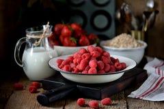 健康早餐是新鲜的有机莓、草莓与燕麦剥落和牛奶在老木背景 土气样式 免版税库存照片