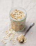 健康早餐有机燕麦在玻璃瓶子灰色纺织品背景中剥落 库存图片