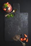 健康早餐框架 Chia在黑板岩的布丁用新鲜的莓果和薄菏向在黑暗的背景的委员会扔石头 免版税库存图片