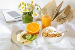 健康早餐概念果子香蕉猕猴桃桔子,与格兰诺拉麦片,在白色背景的橙汁玻璃的酸奶 免版税库存照片