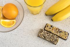 健康早餐橙汁,谷物酒吧,切了桔子,香蕉 免版税库存照片