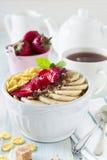 健康早餐玉米片、香蕉、草莓、杏仁、巧克力和酸奶在一个陶瓷碗 免版税库存照片