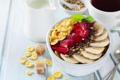 健康早餐玉米片、香蕉、草莓、杏仁、巧克力和酸奶在一个陶瓷碗 库存图片