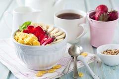 健康早餐玉米片、香蕉、草莓、杏仁、巧克力和酸奶在一个陶瓷碗 图库摄影