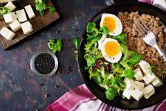 健康早餐用在黑暗的背景的蛋、乳酪、莴苣和荞麦粥 适当的营养 饮食菜单 库存照片