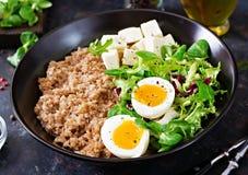 健康早餐用在黑暗的背景的蛋、乳酪、莴苣和荞麦粥 图库摄影