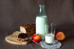 健康早餐用新鲜面包、被抹上的果酱、一杯牛奶和苹果 免版税库存图片