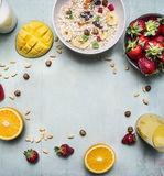 健康早餐用粥,草莓、新鲜的橙汁、芒果和坚果安置文本,在木土气背景的框架 免版税库存照片