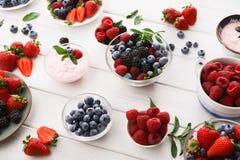 健康早餐用莓果和酸奶在白色木桌上 库存图片