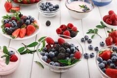 健康早餐用莓果和酸奶在白色木桌上 免版税图库摄影