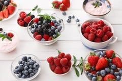 健康早餐用莓果和酸奶在白色木桌上 免版税库存照片