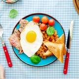 健康早餐用鸡蛋、豆、烟肉、西红柿和sp 免版税库存图片