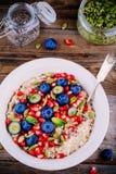 健康早餐碗燕麦粥用新鲜的蓝莓、石榴、薄菏、chia、胡麻和南瓜籽 图库摄影