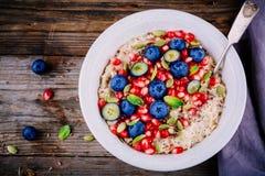 健康早餐碗燕麦粥用新鲜的蓝莓、石榴、薄菏、chia、胡麻和南瓜籽 库存图片