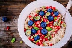 健康早餐碗燕麦粥用新鲜的蓝莓、石榴、薄菏、chia、胡麻和南瓜籽 免版税库存照片