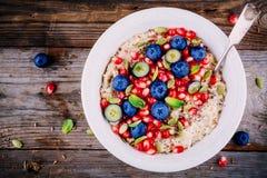 健康早餐碗粥用新鲜的蓝莓、石榴、薄菏、chia、胡麻和南瓜籽 库存照片