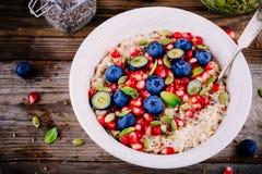 健康早餐碗粥用新鲜的蓝莓、石榴、薄菏、chia、胡麻和南瓜籽 免版税库存照片
