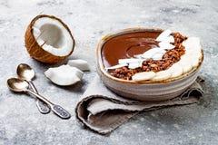 健康早餐碗 巧克力香蕉圆滑的人碗用椰子剥落,格兰诺拉麦片,香蕉切片 免版税库存图片