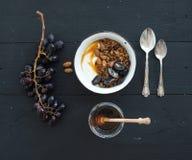 健康早餐集合 碗燕麦格兰诺拉麦片用酸奶、新鲜的葡萄、杏仁和蜂蜜在黑木背景 免版税图库摄影