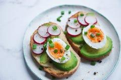 健康早餐,多士用鲕梨,鸡蛋,萝卜,甜葱,饮食食物,在轻的大理石背景,选择聚焦closeu 免版税库存图片