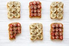 健康早餐,节食的概念 素食主义者多士和一被咬住的多士用果子,种子,花生酱在白色木背景 免版税库存照片