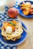 健康早餐:与桃子切片的比利时华夫饼干和奶油装饰了薄荷叶和蓝色餐巾 免版税图库摄影