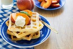 健康早餐:与桃子切片的比利时华夫饼干和奶油装饰了薄荷叶和蓝色餐巾 免版税库存照片