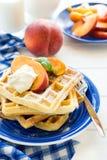 健康早餐:与桃子切片的比利时华夫饼干和奶油装饰了薄荷叶和蓝色餐巾 库存照片