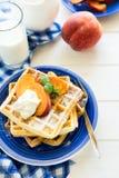 健康早餐:与桃子切片的比利时华夫饼干和奶油装饰了薄荷叶和蓝色餐巾 图库摄影