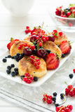 健康早餐:与酸性稀奶油和新鲜的成熟莓果的乳酪薄煎饼 图库摄影
