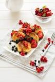 健康早餐:与酸性稀奶油和新鲜的成熟莓果的乳酪薄煎饼 库存图片