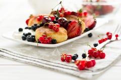 健康早餐:与酸性稀奶油和新鲜的成熟莓果的乳酪薄煎饼 免版税图库摄影