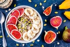 健康早餐:燕麦粥用新鲜的无花果、香蕉、南瓜籽、椰子和chia种子 免版税库存图片