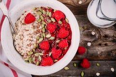 健康早餐:燕麦粥用新鲜的莓、亚麻籽和南瓜籽 免版税图库摄影