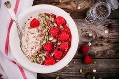 健康早餐:粥用新鲜的莓、亚麻籽和南瓜籽 免版税库存图片