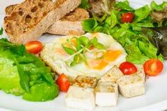 健康早餐-油煎的鹌鹑蛋、鲕梨、沙拉、西红柿、豆腐和面包 免版税图库摄影