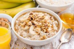 健康早餐-燕麦粥用香蕉、蜂蜜和核桃 免版税库存图片