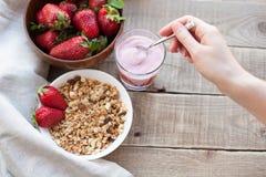 健康早餐Muesli和酸奶用草莓 妇女` s手在muesli投入几勺酸奶 免版税库存图片