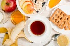 健康早餐Muesli,茶,蜂蜜,曲奇饼,苹果和 免版税库存图片