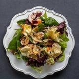 健康有机沙拉顶视图在白色板材的在黑暗的backgro 库存图片