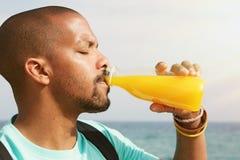 健康有机饮料 喝鲜美新鲜的橙汁的深色皮肤的人画象 非洲人坐温暖 库存图片