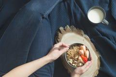 健康有格兰诺拉麦片、草莓和坚果的早餐灰色陶瓷碗在妇女` s手上 饮食和素食主义者食物概念 免版税图库摄影
