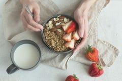 健康有格兰诺拉麦片、草莓和坚果的早餐灰色陶瓷碗在妇女` s手上 饮食和素食主义者食物概念 库存照片