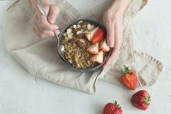 健康有格兰诺拉麦片、草莓和坚果的早餐灰色陶瓷碗在妇女` s手上 饮食和素食主义者食物概念 图库摄影