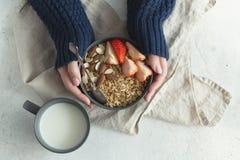 健康有格兰诺拉麦片、草莓和坚果的早餐灰色陶瓷碗在妇女` s手上 饮食和素食主义者食物概念 库存图片